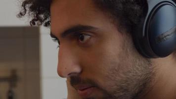 Nahaufnahme des jungen nahöstlichen Mannes, der in der Küche steht, Kopfhörer auf seiner Hand, eine Hand auf Ohrabdeckung, seinen Kopf bewegend