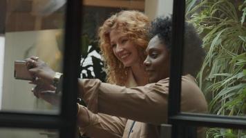 mulher negra madura faz foto com o celular dela e uma jovem branca em pé ao lado dela, sorrindo, no corredor