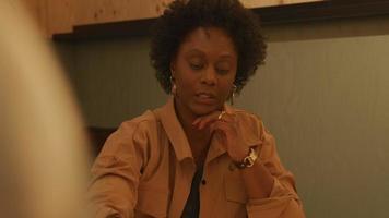 mulher negra madura e jovem branca sentada à mesa, conversando no escritório