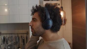 junger Mann aus dem Nahen Osten steht in der Küche, Kopfhörer auf dem Kopf, beide Hände auf der Ohrbedeckung, eine Hand auf der Decke, bewegt seinen Kopf
