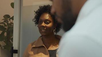 schwarze reife Frau spricht und schaut auf Tablette, gehalten von schwarzem Mann im Vordergrund video