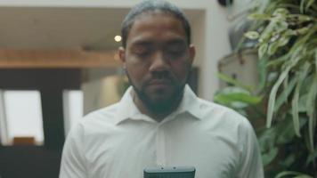 homme noir debout et regardant le téléphone portable devant lui, les yeux de l'homme se tournent vers la caméra, sourires video