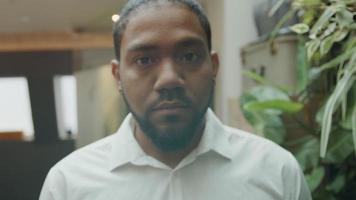 homme noir debout, la tête tournée vers le bas, lève la tête, les yeux regardant dans la caméra video