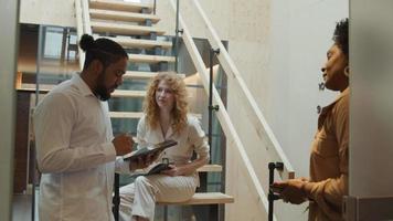 homem negro com tablet, mulher negra madura e jovem branca conversando no corredor