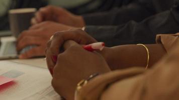 fechar as mãos na mesa de uma mulher negra madura, segurando uma caneta video