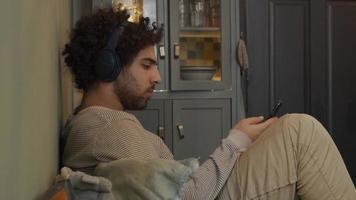 jovem homem do Oriente Médio com fone de ouvido na cabeça, move a cabeça, senta, flexiona as pernas, segura e assiste ao celular, canta um pouco