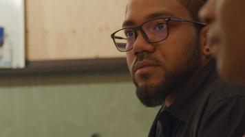 svart man bär glasögon och svart mogen kvinna bredvid honom, pratar och lyssnar, på kontoret