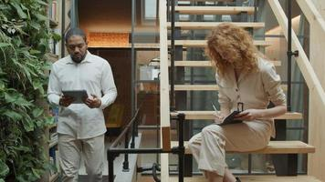svart man går med tablett visar det för ung vit kvinna som sitter i trappsteg och skriver, svart mogen kvinna står och tittar på dem video