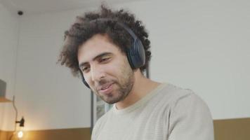 jovem homem do Oriente Médio com fone de ouvido na cabeça, dançando música na sala de estar, rindo