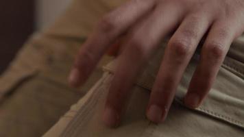 close-up dos dedos de um jovem homem do Oriente Médio batendo no colo, close-up do homem com fone de ouvido sorrindo