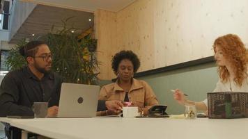mulher madura negra, jovem branca e homem negro de óculos, sentado à mesa, em reunião no escritório
