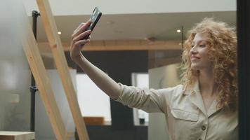 ung vit kvinna håller mobiltelefonen i luften, justerar håret, ler för att ringa, flyttar telefonen framför sig, tittar på skärmen video