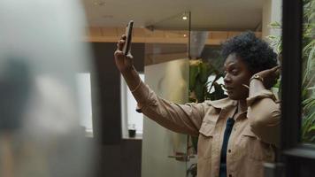 mulher madura negra segurando o celular no ar, ajeitando o cabelo, olhando para o telefone video