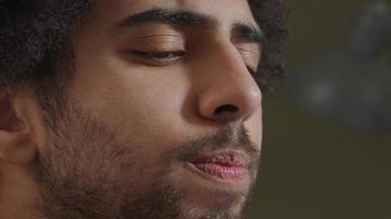 extreme Nahaufnahme des Gesichts des jungen Mannes aus dem Nahen Osten, der konzentriert aussieht