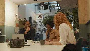 mulher madura negra, jovem branca e homem negro de óculos, sentado à mesa no escritório, conversando, gestos de mulher branca