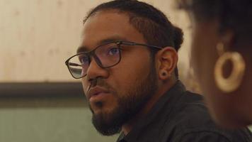 homem negro de óculos, fala, olha para uma mulher negra madura em primeiro plano