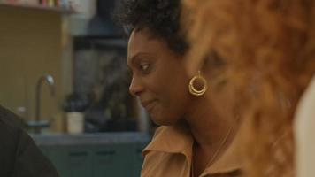 mulher madura negra, jovem branca e homem negro de óculos, sentado à mesa no escritório, assistindo a brochura na mesa