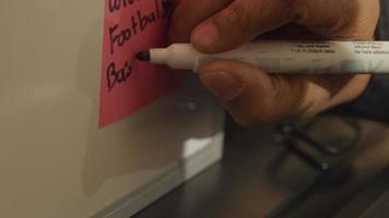 Cerca de la mano del hombre negro, escribiendo con marcador en papel pegado en una pizarra blanca video