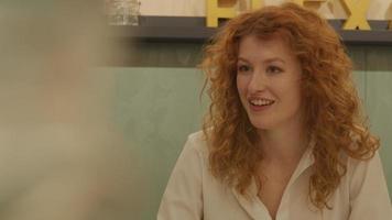 witte jonge vrouw zit aan tafel in kantoor, praten, gebaren, glimlachen video