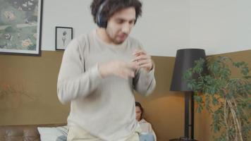 jovem homem do Oriente Médio com fone de ouvido dança expressivamente na música na sala de estar, jovem mulher mestiça no sofá lendo