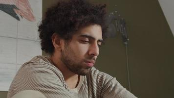 ung man från Mellanöstern sitter på sängen, bärbar dator framför honom och tänker kontemplativt och skriver video
