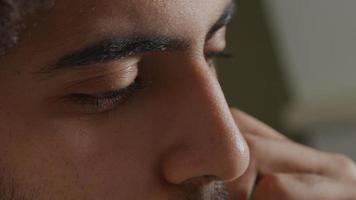 extreme Nahaufnahme des Gesichts eines jungen Mannes aus dem Nahen Osten, der konzentriert aussieht und die Finger den Bart berührt