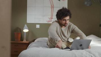 Der junge Mann aus dem Nahen Osten sitzt auf dem Bett und spricht mit dem Laptop vor ihm