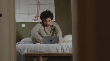 Jeune homme du Moyen-Orient est assis sur le lit, ordinateur portable en face de lui, tapant video