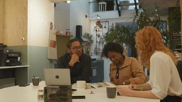 mulher madura negra, jovem branca e homem negro de óculos, sentado à mesa no escritório, conversando e assistindo a brochura na mesa