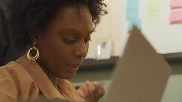 Femme mature noire s'assoit et parle, la tête tournée vers l'homme noir, qui se tient à côté d'elle, la femme tourne la tête en regardant la table, en parlant, au bureau video