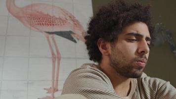 Der junge Mann aus dem Nahen Osten sitzt auf dem Bett, den Laptop vor sich, sieht konzentriert aus und tippt
