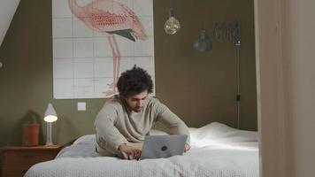 ung man från Mellanöstern sitter på sängen, bärbar dator framför honom, mumlar och skriver video