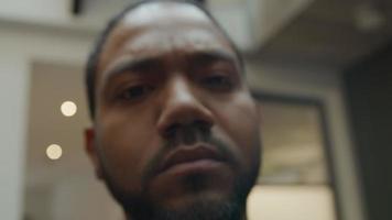 närbild av svart man som ser allvarligt in i kameralinsen