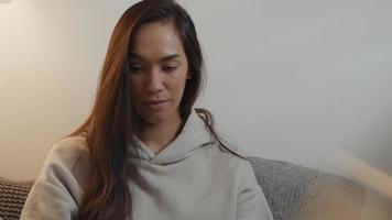 jovem mestiça sentada na sala de estar, vendo e tocando a tela do tablet na perna video