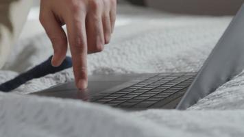 Gros plan d'un ordinateur portable sur le lit et les mains d'un jeune homme du Moyen-Orient, défilement sur le pavé tactile et clavier de saisie video
