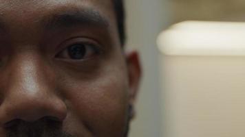 extrem närbild av ögonbryn, öga och näsa av svart man, ögon blinkar, öga tittar in i kameran