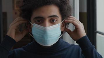 close-up de um jovem homem do Oriente Médio, olhando pelas lentes da câmera, colocando uma máscara facial video
