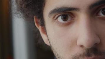 close extremo da parte esquerda do rosto de um jovem homem do Oriente Médio, levanta a cabeça, olhos olhando para a câmera video