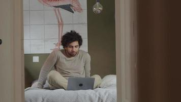 jovem homem do Oriente Médio sentado na cama, laptop na frente dele, conversando online, arrumando o cabelo e conversando video