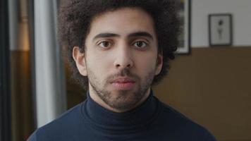 Gros plan du jeune homme du Moyen-Orient, regardant vers le bas, lève la tête, les yeux regardant sérieusement dans l'objectif de la caméra video