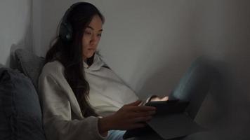 Die junge Frau mit gemischten Rassen sitzt auf der Couch in der Ecke des Wohnzimmers und beobachtet den Bildschirm des Tablets vor sich. Der Bildschirm wird auf Gesicht und Augen reflektiert
