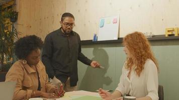 svart mogen kvinna och vit ung kvinna sitter vid bordet, svart man bär glasögon står i mitten och pratar i kontorsmöte