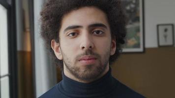 close-up de jovem homem do Oriente Médio, olhos olhando seriamente para as lentes da câmera video