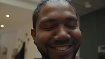 close-up de um homem negro olhando pela lente da câmera, rindo