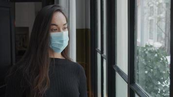 Jeune métisse femme avec masque à côté de la fenêtre regarde à travers la fenêtre, se tourne légèrement vers la fenêtre video