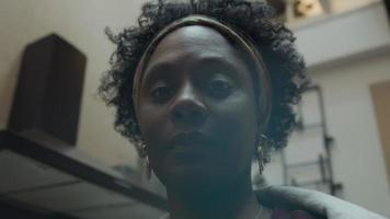 close-up de uma mulher negra madura em pé, olhos seguindo as lentes da câmera video