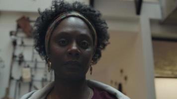 svart mogen kvinna står i korridoren, närbild av hennes ansikte tittar in i kameran