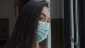 Close up of young mixed race woman with face mask on, à côté de la fenêtre, regardant à travers la fenêtre video
