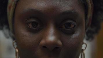 extrem närbild av ögonbryn, ögon och näsa av svart mogen kvinna, tittar in i kameran, ögon blinkar en gång
