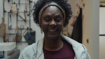 huvudskott av svart mogen kvinna som står i korridoren, ser in i kameralinsen, skrattar